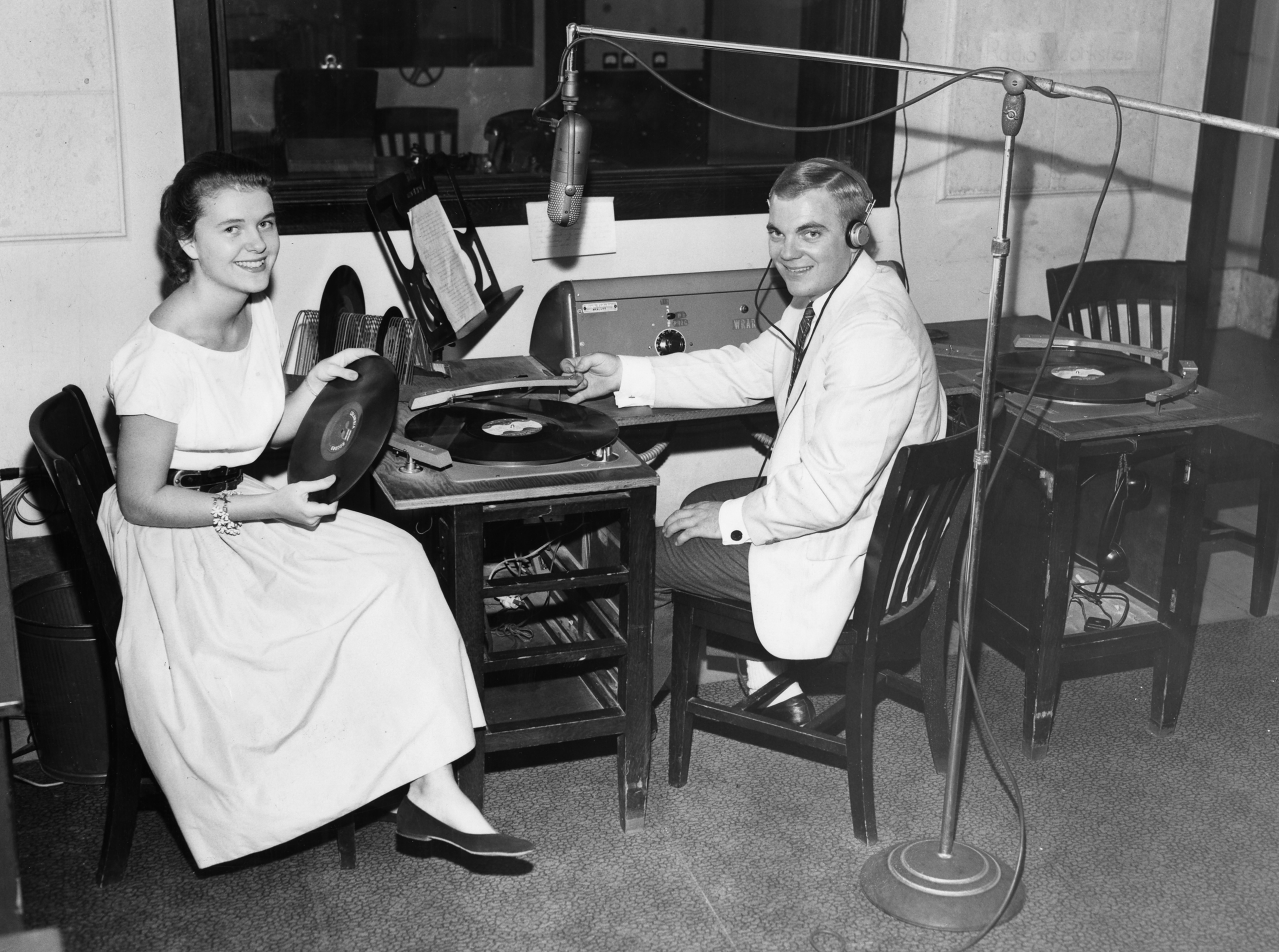 A black and white photograph of students playing records on-air at WRAR in 1957.