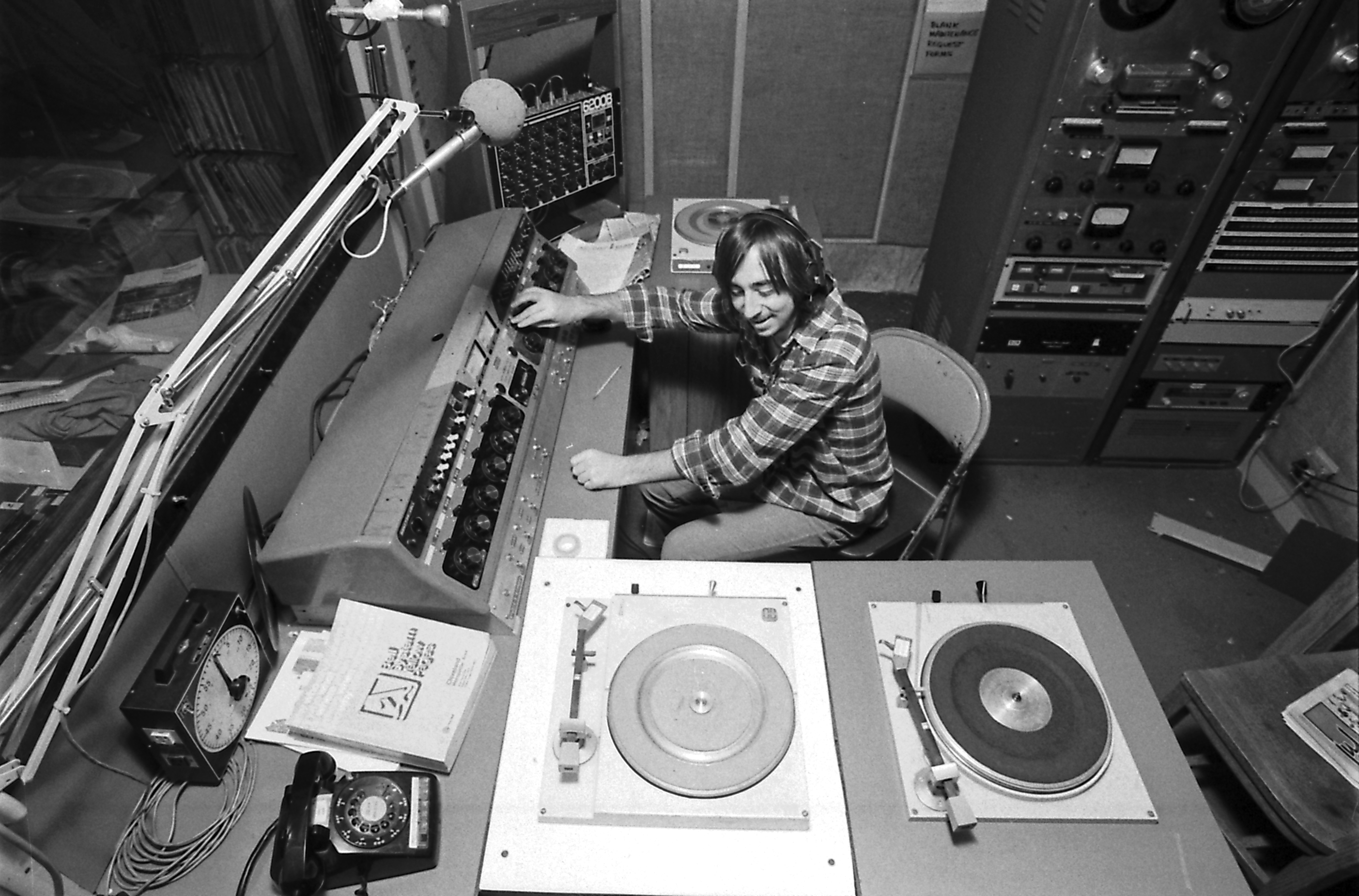 Black and white photograph of a man playing records at radio station WRUW in November 1980.