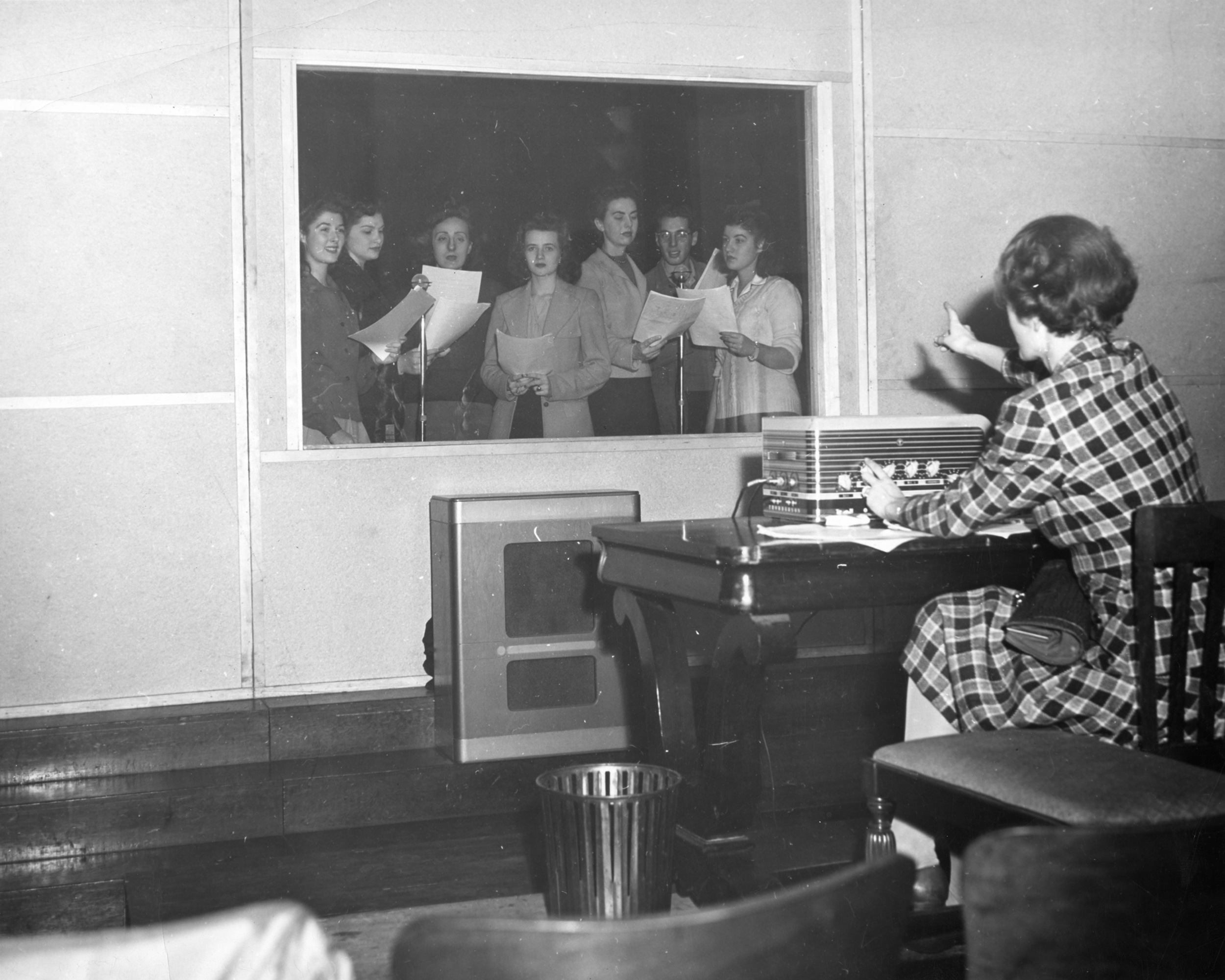 A photograph from 1947 of a woman  from Flora Stone Mather College singing in a radio sound booth and their instructor, Miss Bishop, engineering the broadcast from outside of the radio booth.