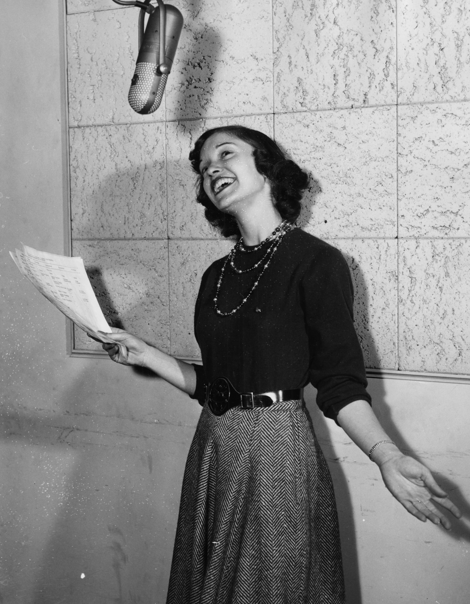 Black and white photograph of a woman named Jean Miller in the WRAR sound booth.