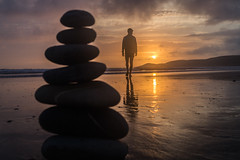 photo of a person on a beach with a constructed pile of stones