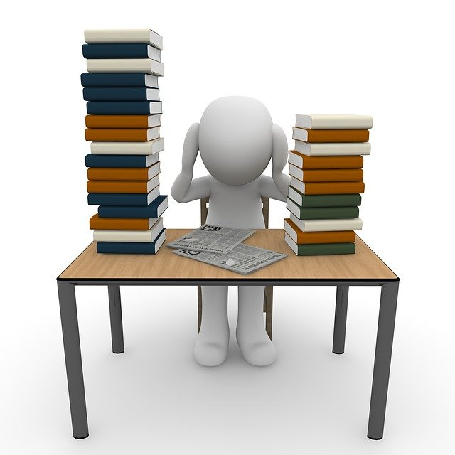 A human figure sitting at a desk with two stacks of books and two newspapers. The human figure appears to be overwhelmed.