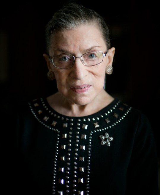 Portrait of Ruth Bader Ginsburg. She is against a black background, wearing a black top with metallic adornments. Her hair is pulled back low in her signature style. She is wearing glasses and looking directly at the camera. She is not smiling.