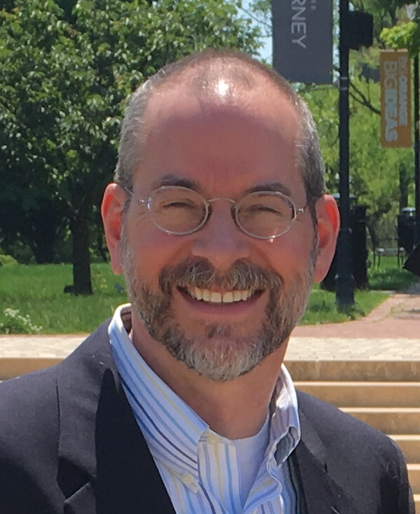 Photo of a smiling man with glasses and a beard wearing a white shirt with a blue jacket in front of some trees