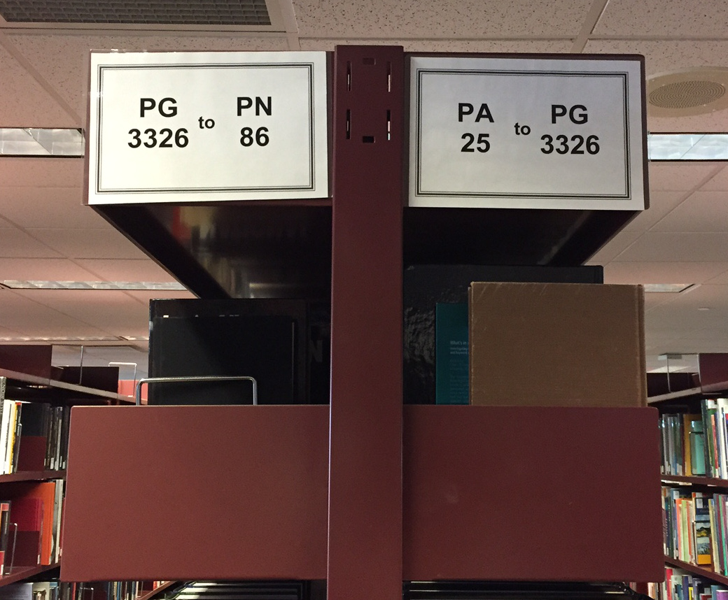 Library shelving unit with shelf range signs listed