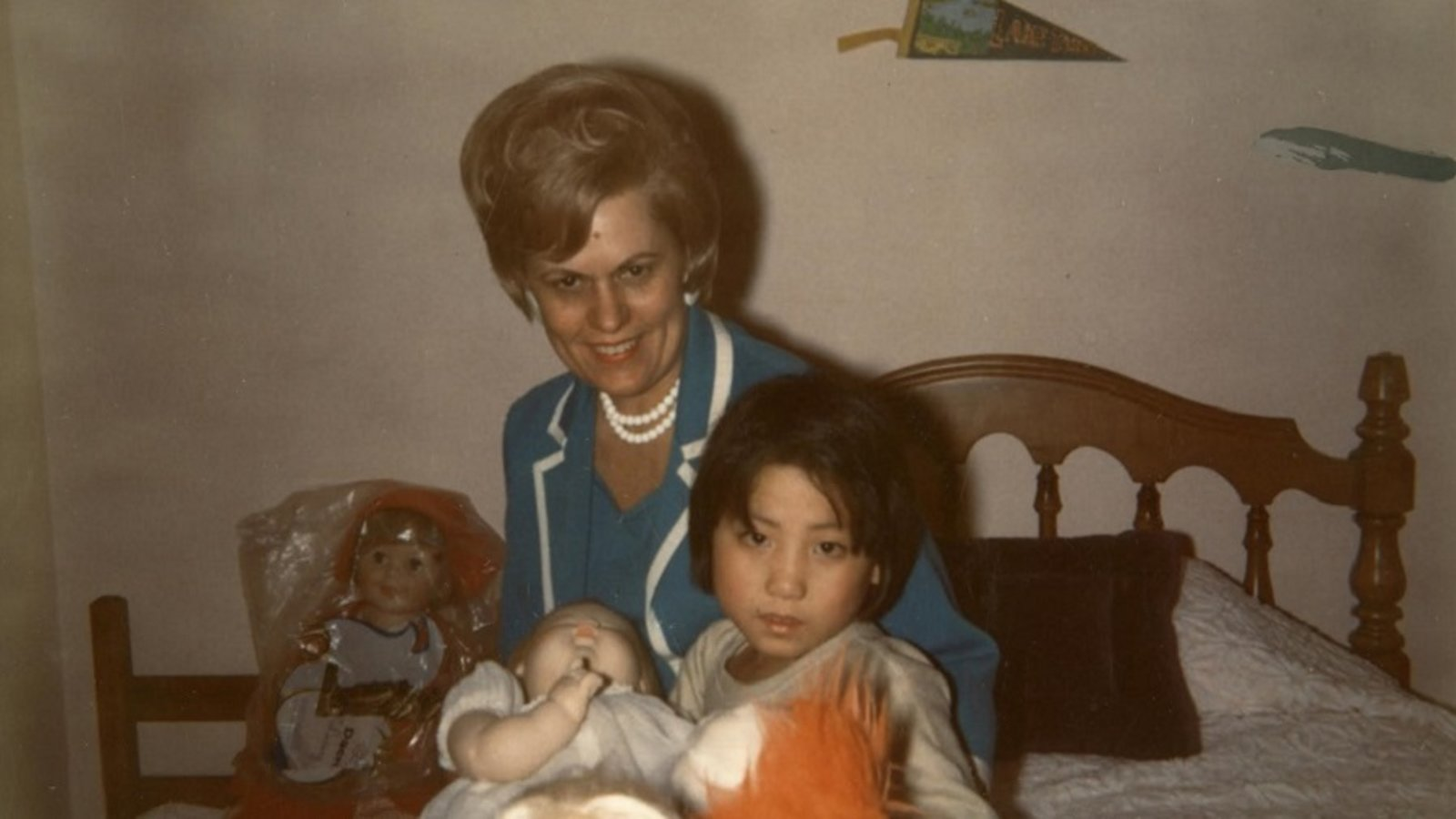 Video still from the film First Person Plural, with a young Korean girl sitting with a white woman on a bed in a child's bedroom