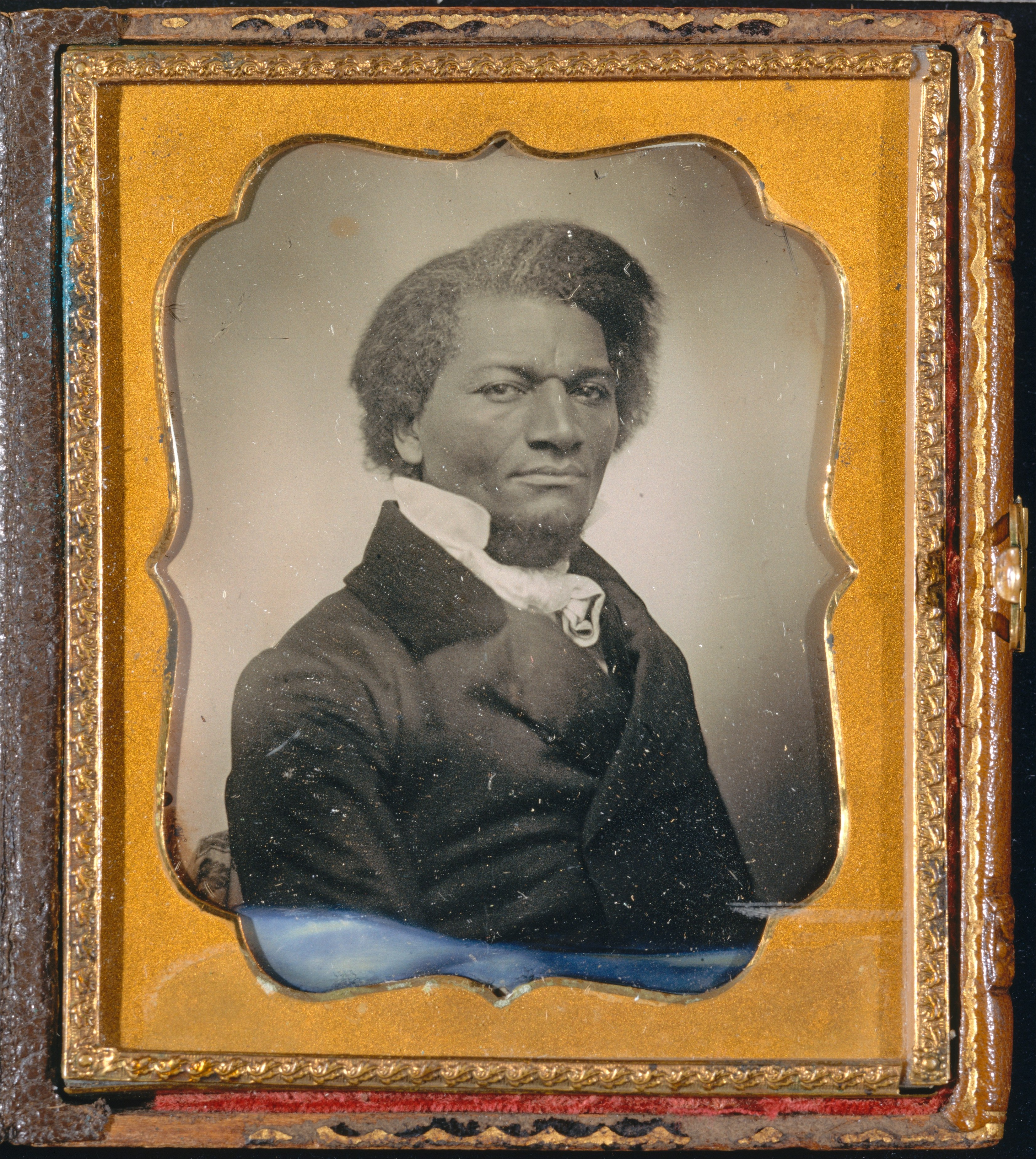 Black and white photograph of Frederick Douglass in a gold frame