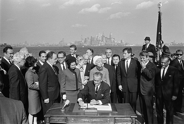 Photograph of US President Lyndon B. Johnson signing the 1965 Hart-Cellar Act