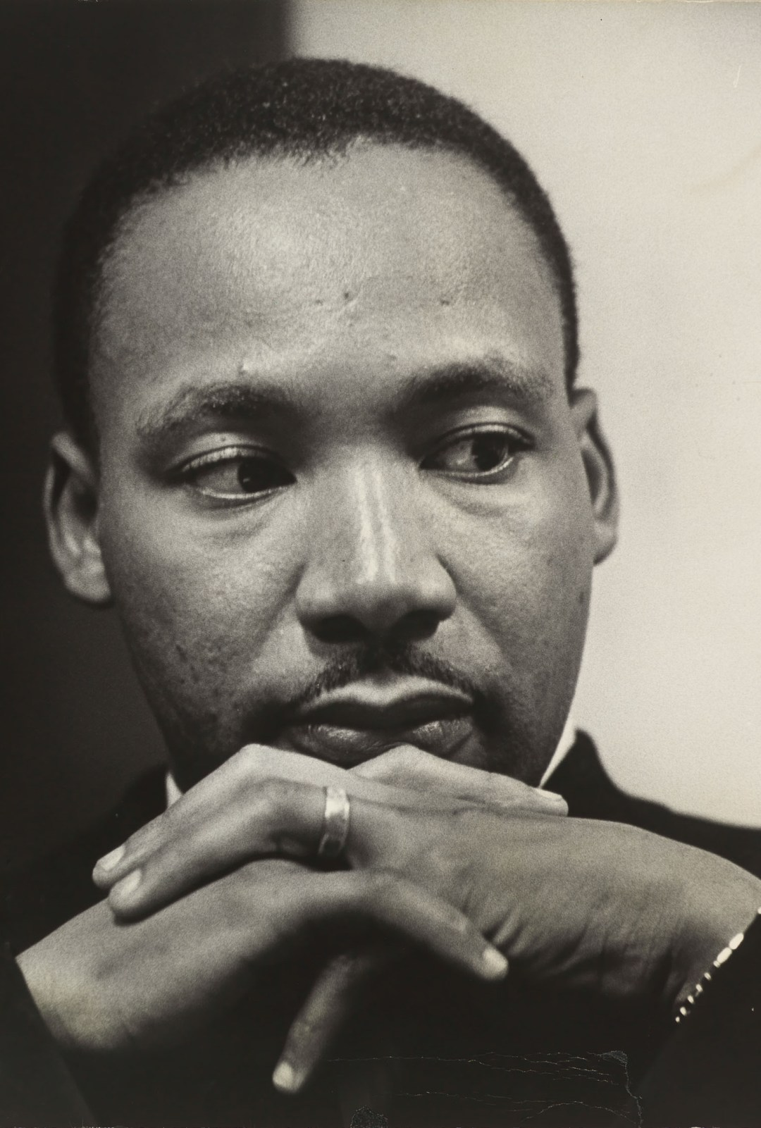 Black and white photographic portrait of Martin Luther King, Jr. looking slightly to the right