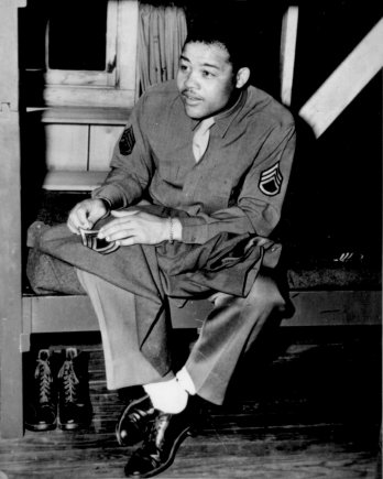 Image of Joe Louis in US Army uniform. Full body shot of man seated looking to the left of the screen.