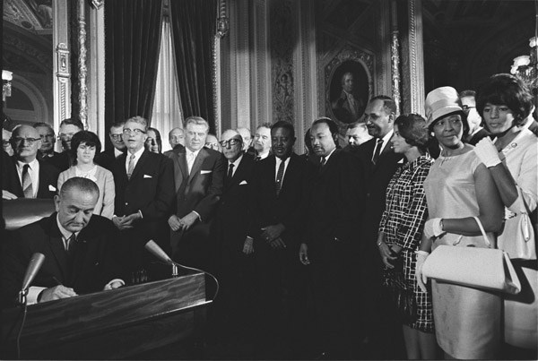 Black and white photo, President Johnson signs the 1965 Voting Rights Act