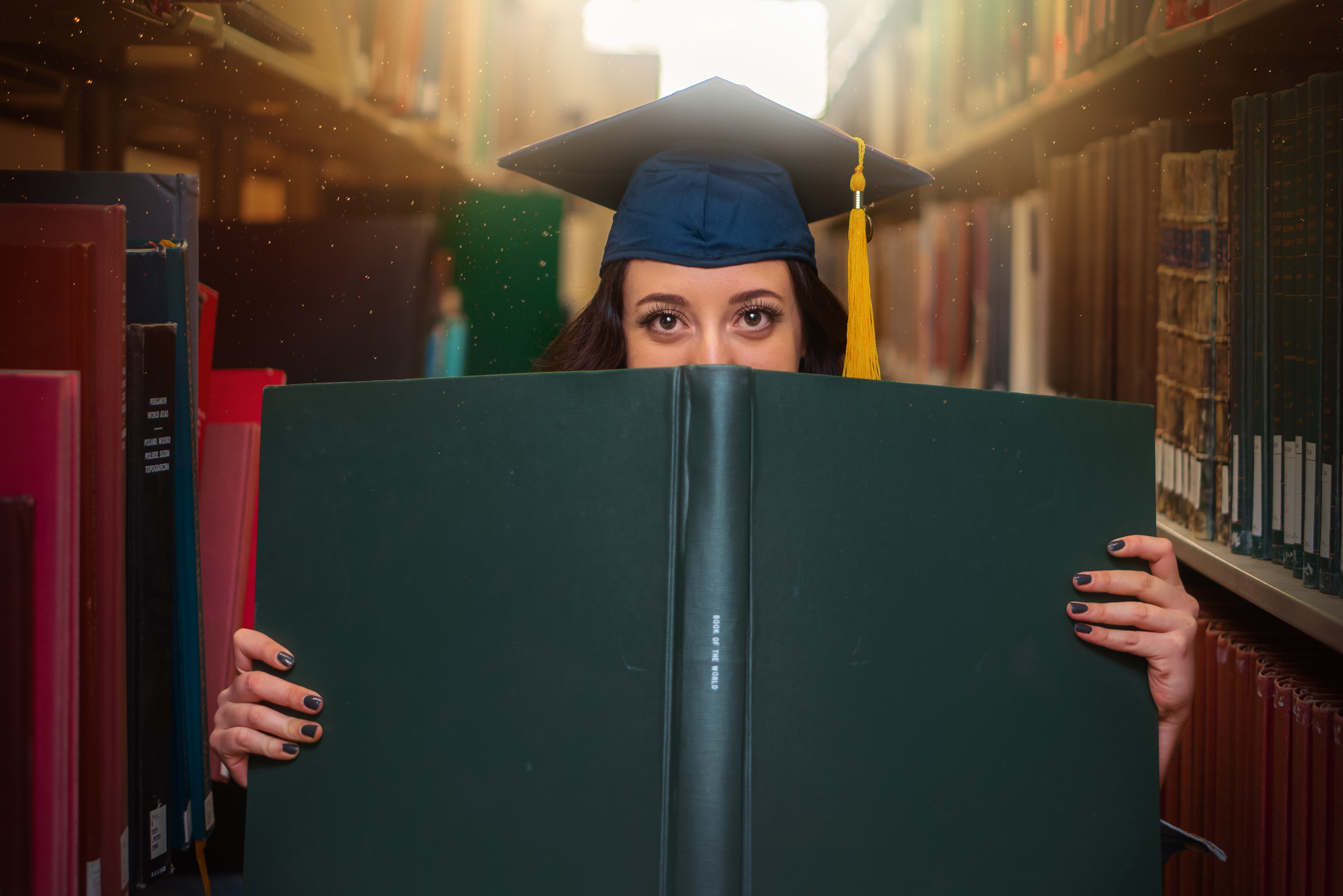 Between library shelves, a woman wearing a graduation cap looking over the top of a book.