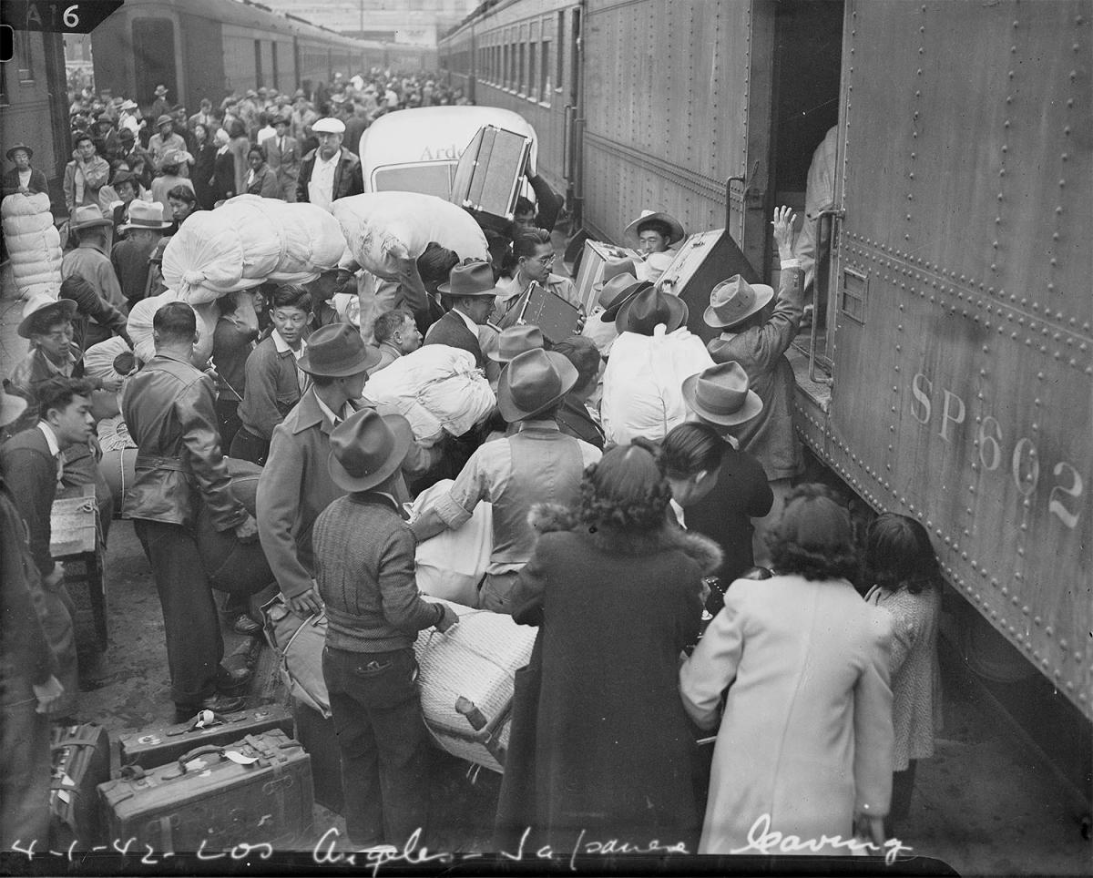 Photo of Japanese Americans boarding train in San Francisco heading to internment camps during World War II