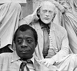 Author James Baldwin in front of a statue of author William Shakespeare