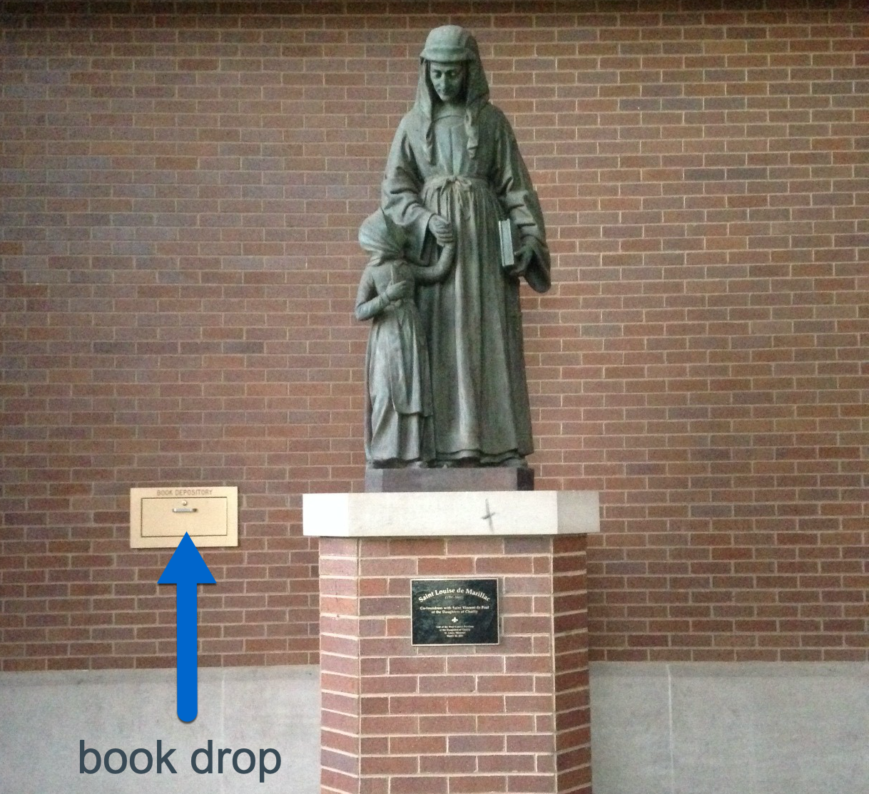 Image Shows rectangular bronze book drop drawer embedded in brick all behind the Louise de Marillac statue on the west quad side of the John T. Richardson Library