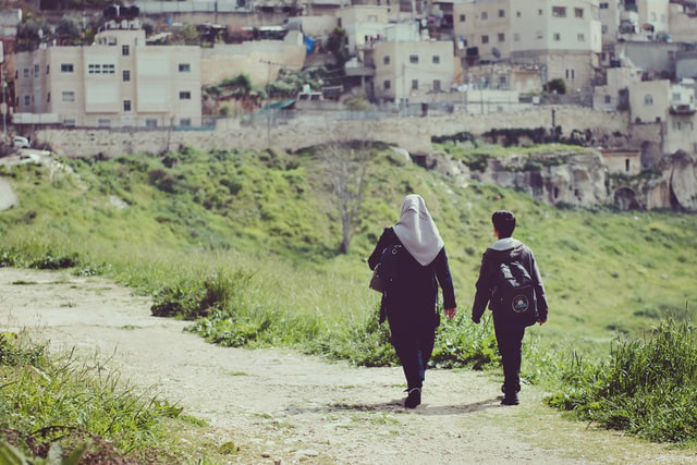 Woman in hijab and boy walk towards a village