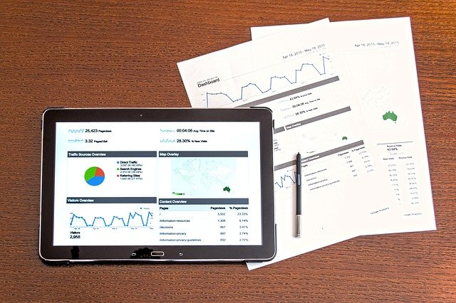 ipad displaying data graphs, two papers with other data graphs displayed