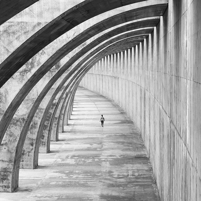 Arching concrete building architecture black and white with distant person walking