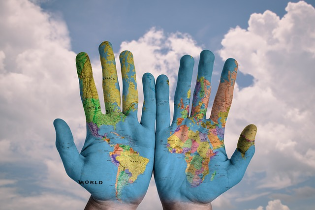 image of blue sky with clouds in the background, in the foreground human hands painted with a map of the world