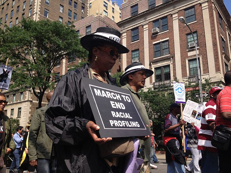 """Protest march with man and woman holding up sign that says """"March to End Racial Profiling."""""""