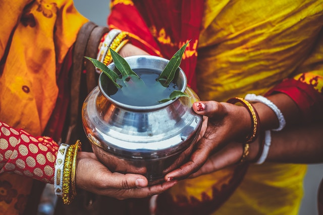 Women dressed in mustard colored saris with their hands wrapped around a metal pot.