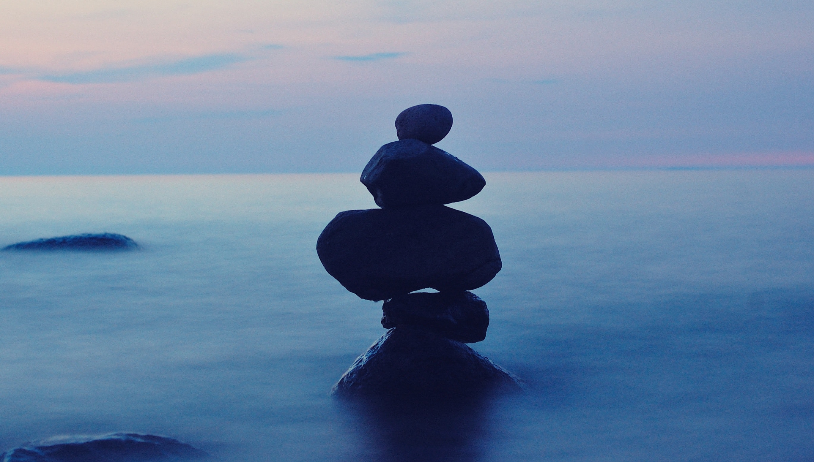 Rocks balanced on top of each other in body of water
