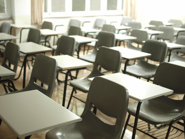 School classroom with rows of empty desks and chairs
