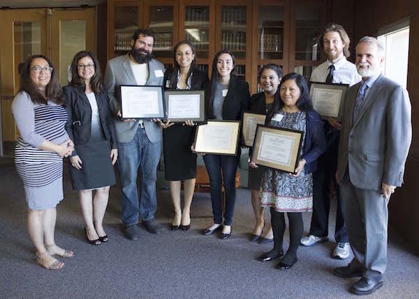 A group photo of previous CSUSM library award winners with students holding framed awards and faculty