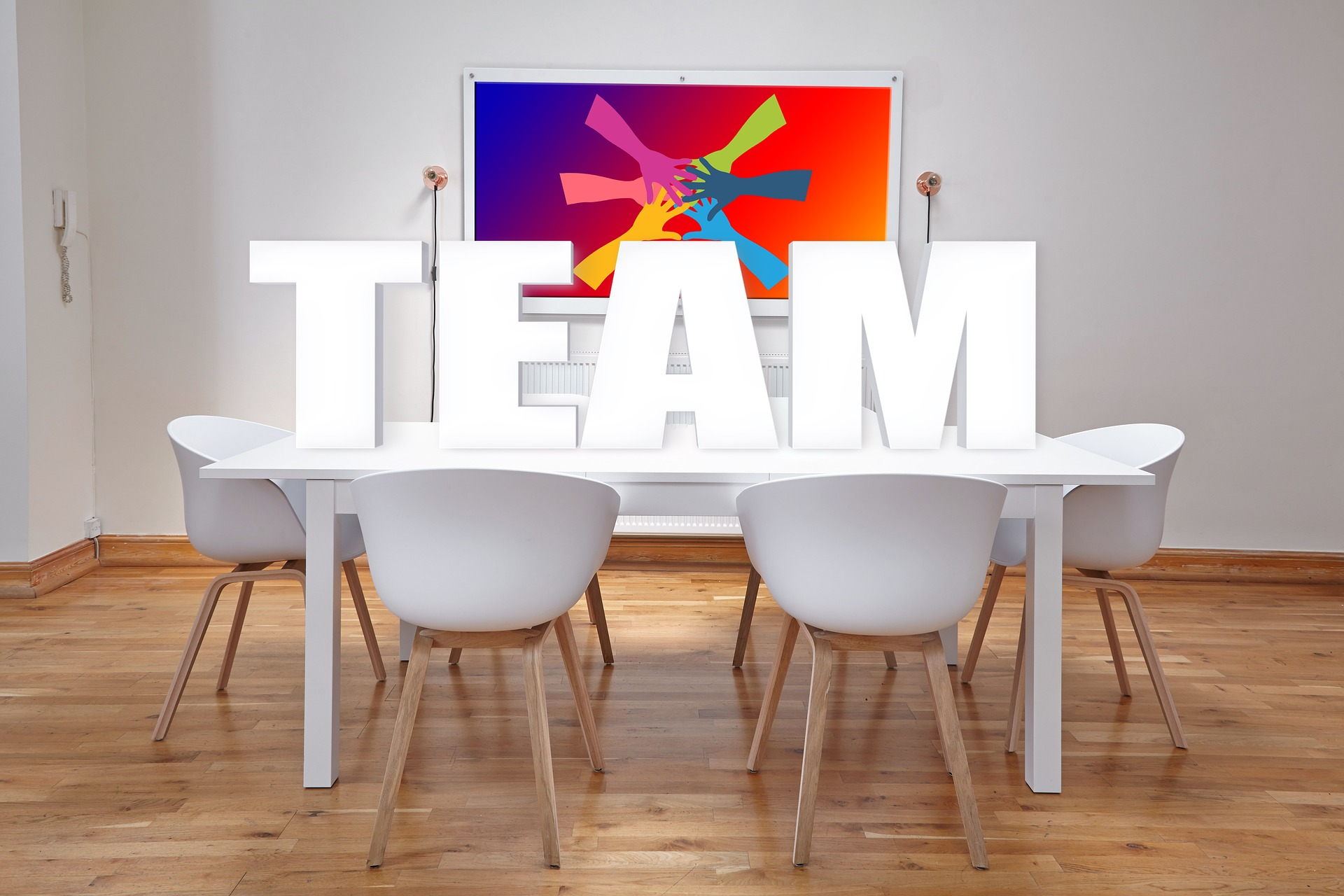 Image of meeting room with table and chairs with the word team on the table
