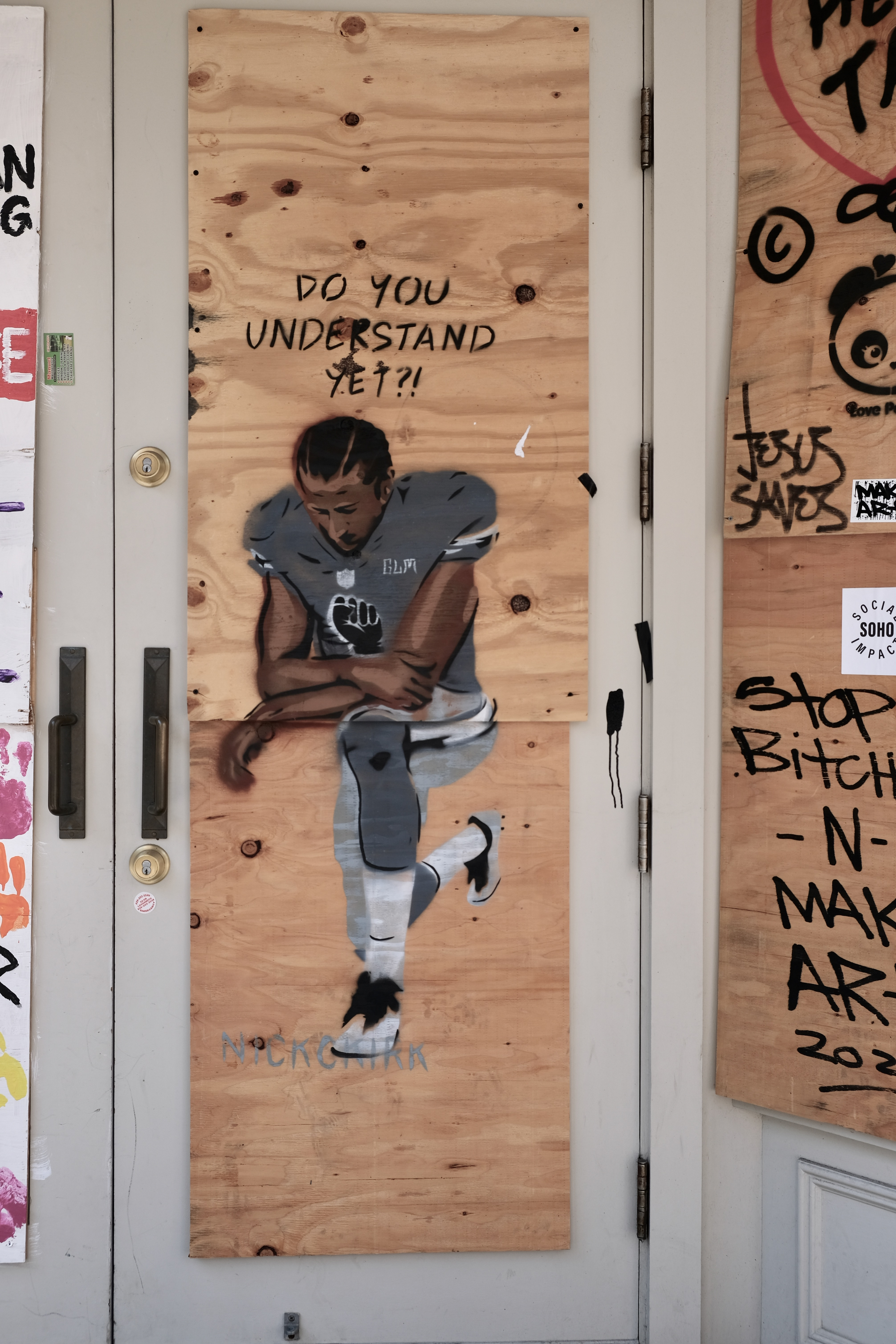 """A picture of a spray painting of Colin Kaepernick, kneeling with a caption saying """"Do you understand yet?!"""""""