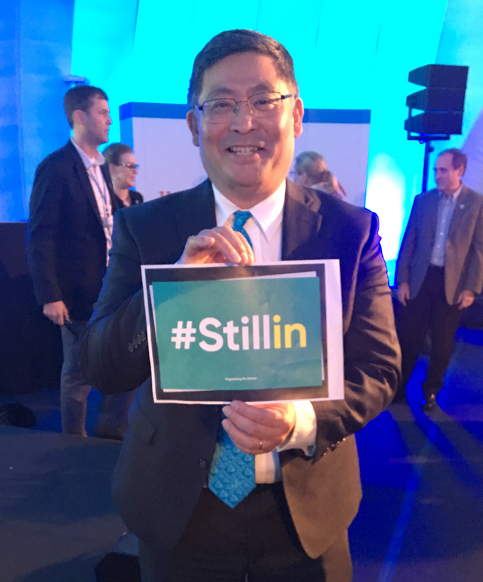 """President Mitsui holding """"still in"""" sign"""
