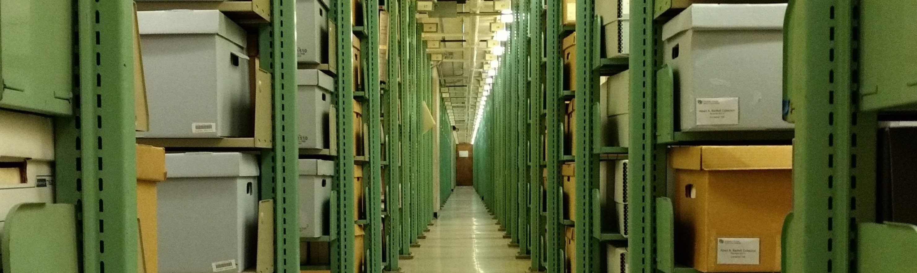 Photograph of CU Boulder Libraries archives stacks, long aisle of green metal shelves filled with labeled cardboard boxes