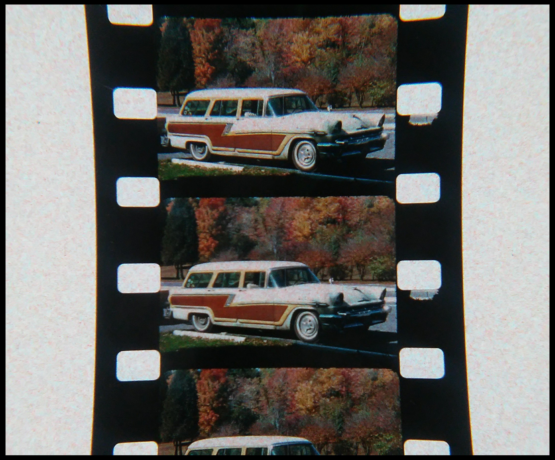 Close-up photograph of 16mm film strips with image of 1950s station wagon in an autumn wood