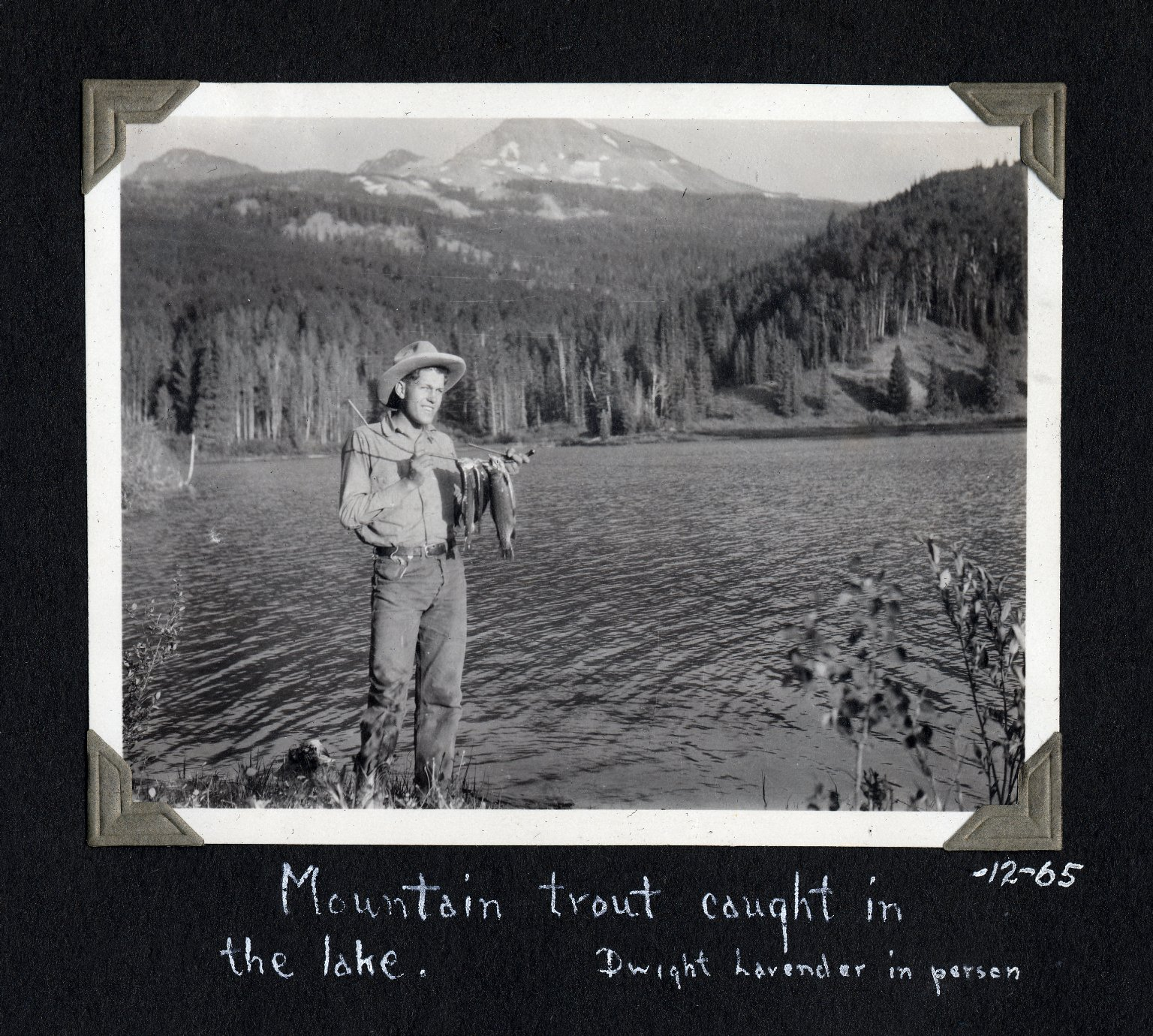 "Black and white photograph of man holding fish, with lake and mountain in the background. Photograph pasted into scrapbook page, with hand written caption ""Mountain trout caught in the lake. Dwight Lavendar in person."""
