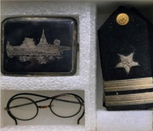 Box, padded with cutout styrofoam, contains a military medal, a pair of round eyeglasses, and a small decorative cigarette case