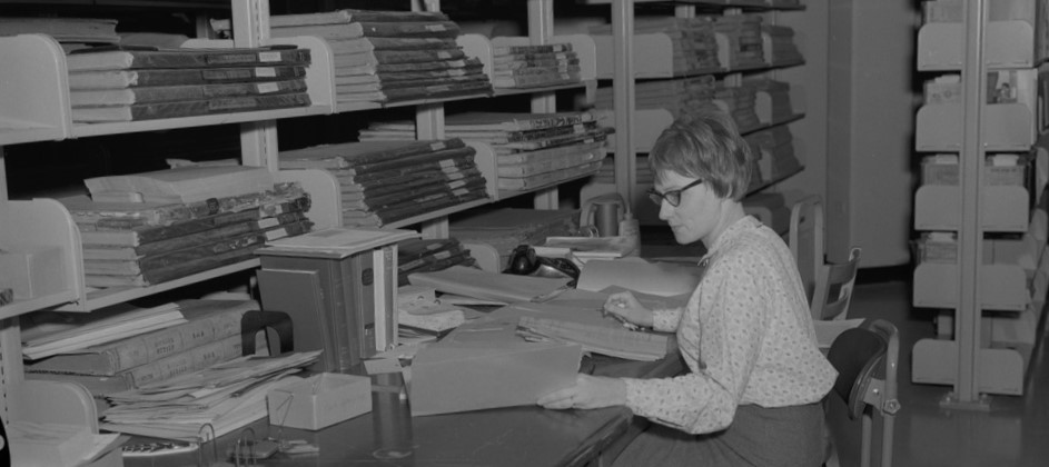 Black and white photograph of woman in CU Boulder archives stacks, looking through documents
