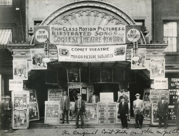 """Black and white photograph of Comet Theater building exterior with many illustrated banners and placards reading """"High Class Motion Pictures and Illustrated Songs,"""" and announcing movie titles"""