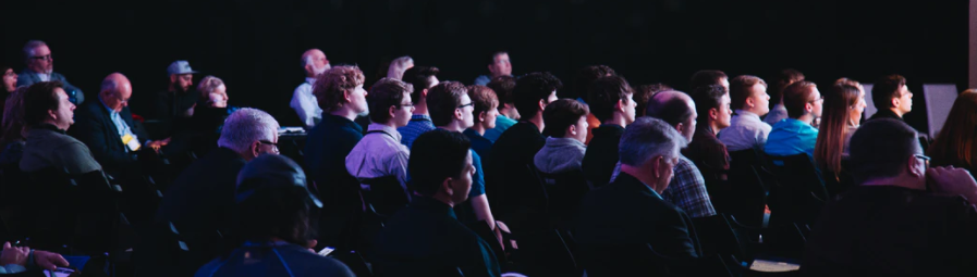 ornamental image of an audience at what appears to be one of those TED talk things