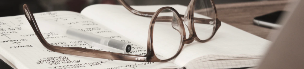 ornamental image of a set of reading glasses lying on a book