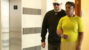 A woman is a sighted guide for a blind man.