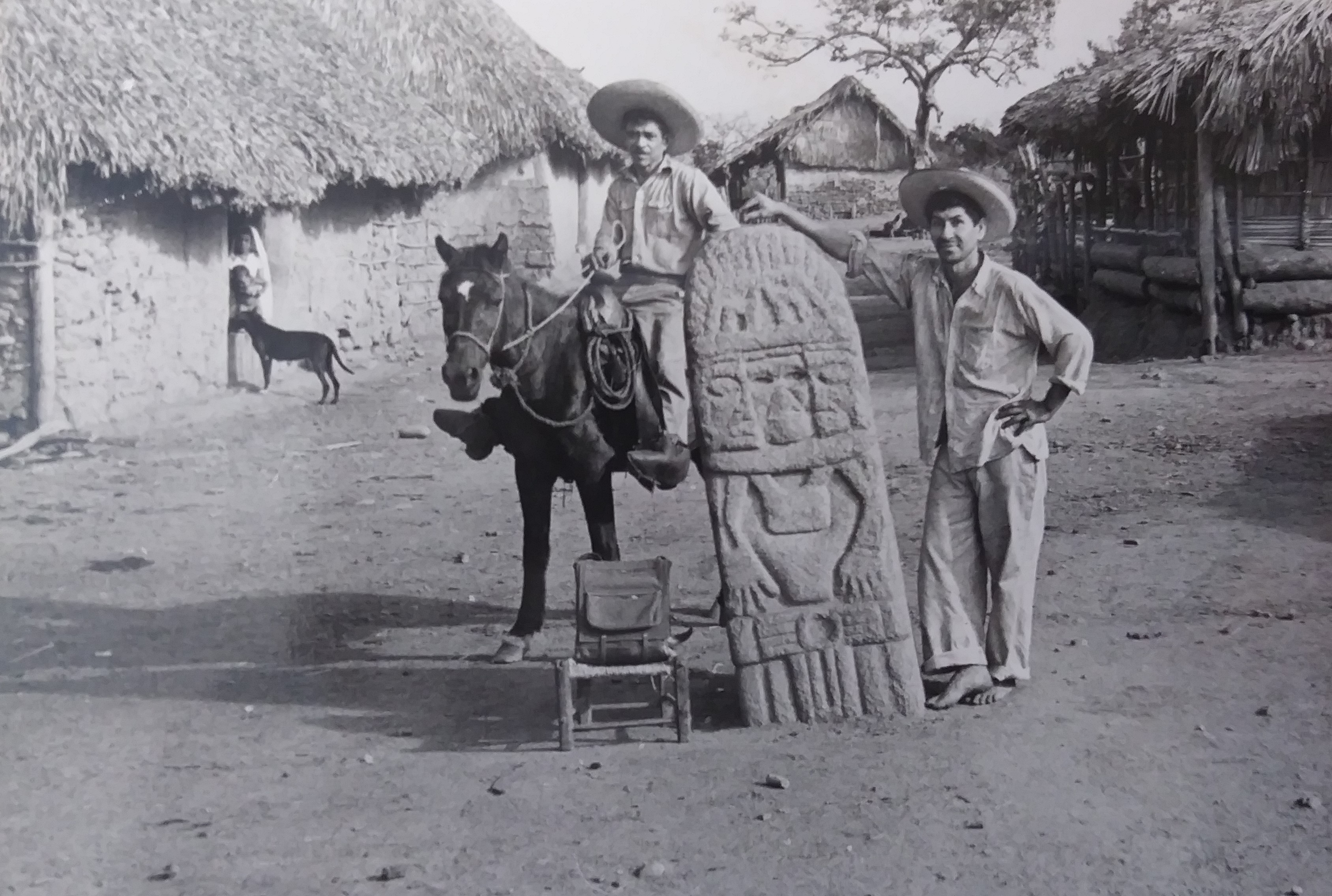 Two men, one standing and one sitting on a horse, with a stele in La Soledad de Maciel, Guerrero, Mexico
