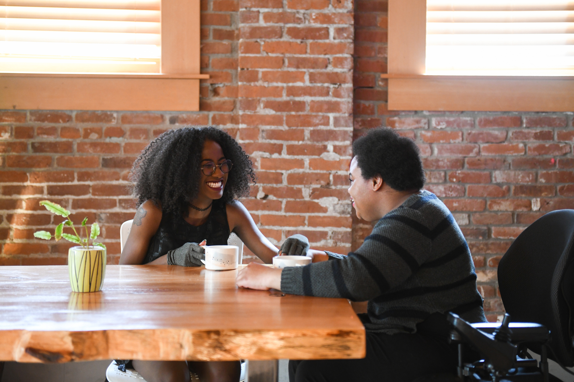 Two disabled Black people (a femme wearing compression gloves and a non-binary person in a power wheelchair that's partially in view) sit across each other and laugh while on a coffee date in a brick building.