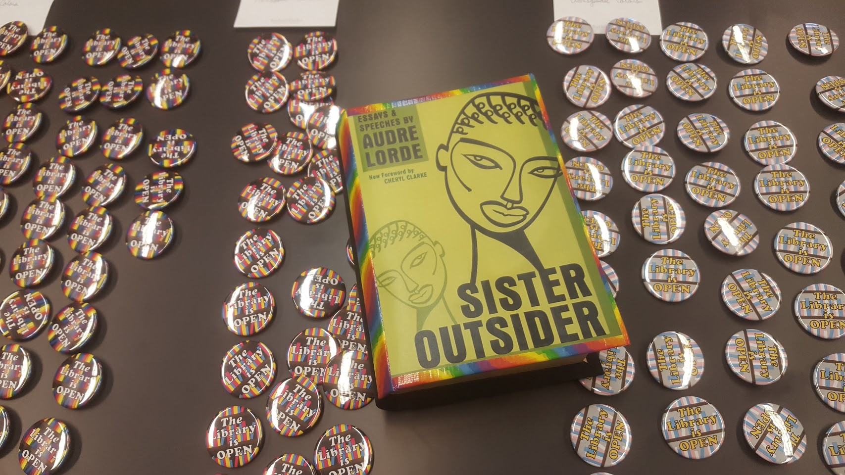 ISU Library's Pridefest buttons and facsimile book for Pridefest 2020