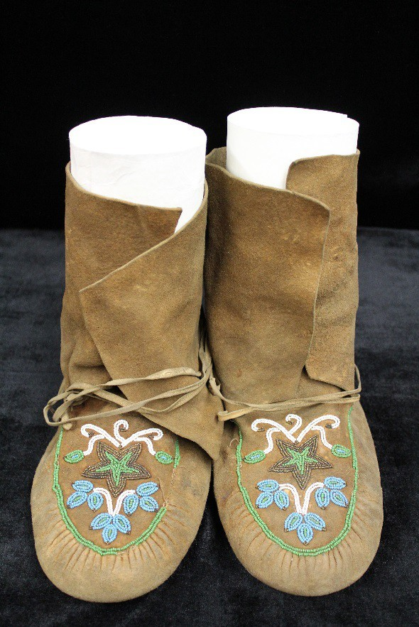 A pair of hide moccasins with beadwork in the design of flowers and a star.