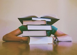 book pile with student