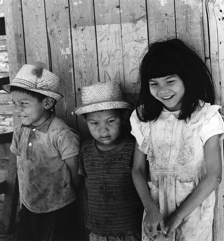 Native American Community series: Three Native American children against wood wall.