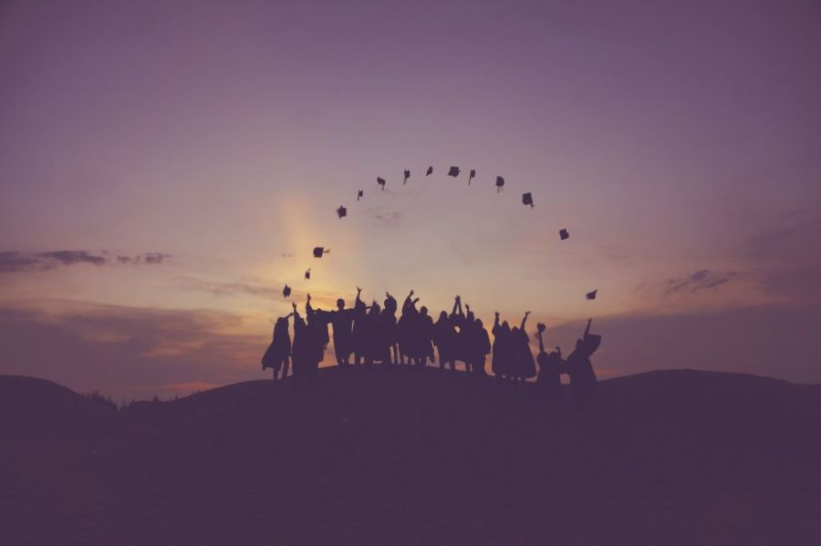 Students throwing graduation caps into the sky