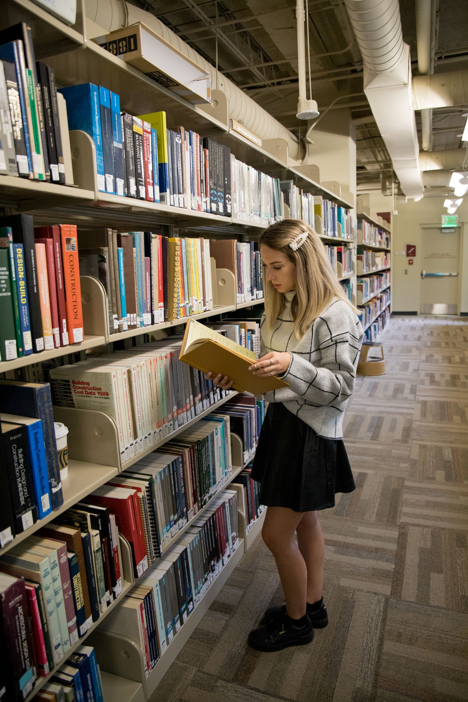 A student looking at a book next to a bookshelf.