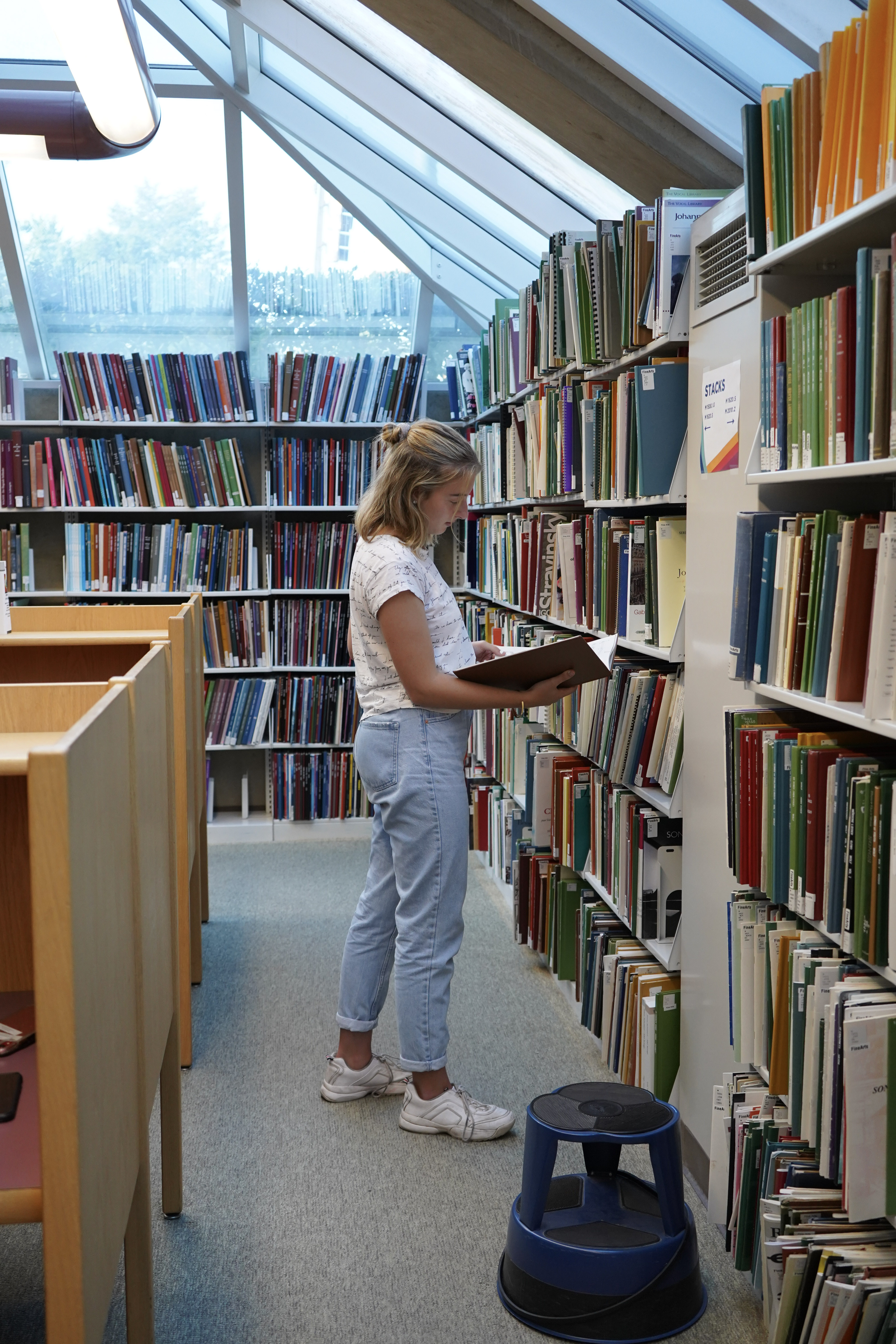 A student browsing the bookshelves under a skylight.