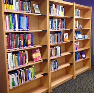 3 library bookshelves with print, audio, video materials